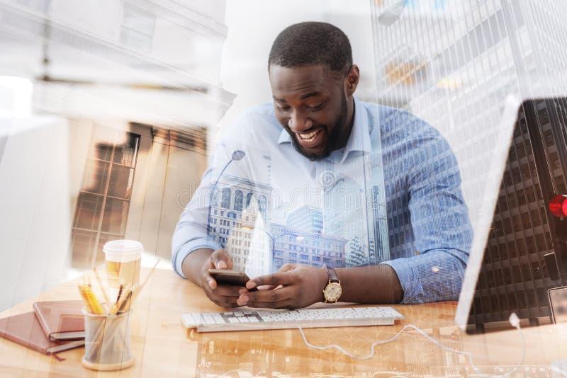 Opgewekte Afrikaanse Amerikaan die mobiele telefoon met behulp van royalty-vrije stock afbeeldingen
