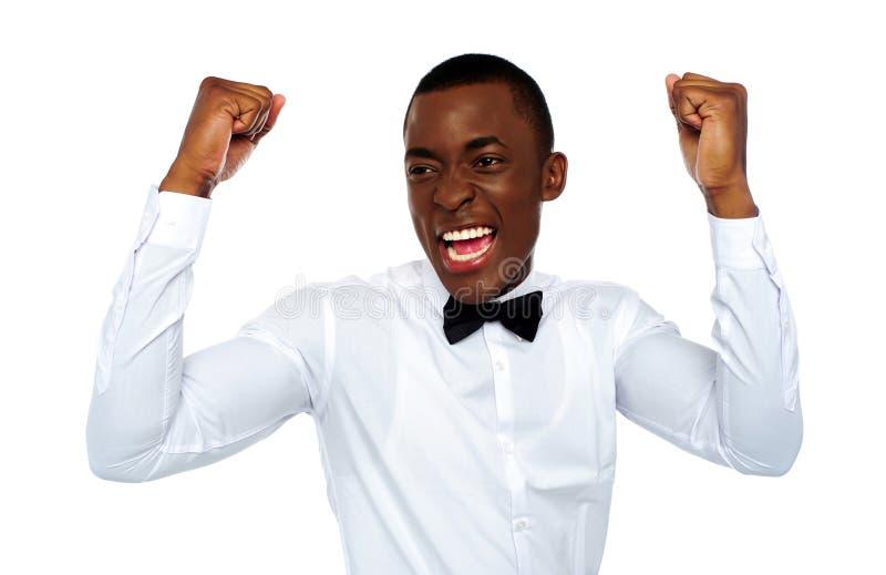 Opgewekte Afrikaanse mens die van zijn succes geniet stock afbeeldingen