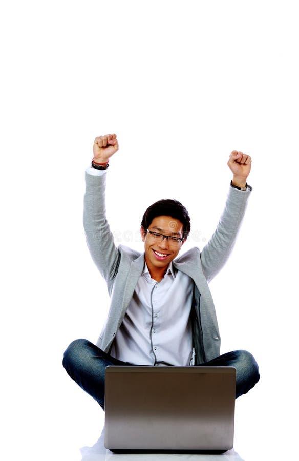 Opgewekte Aziatische mens die laptop op de vloer met behulp van royalty-vrije stock afbeelding