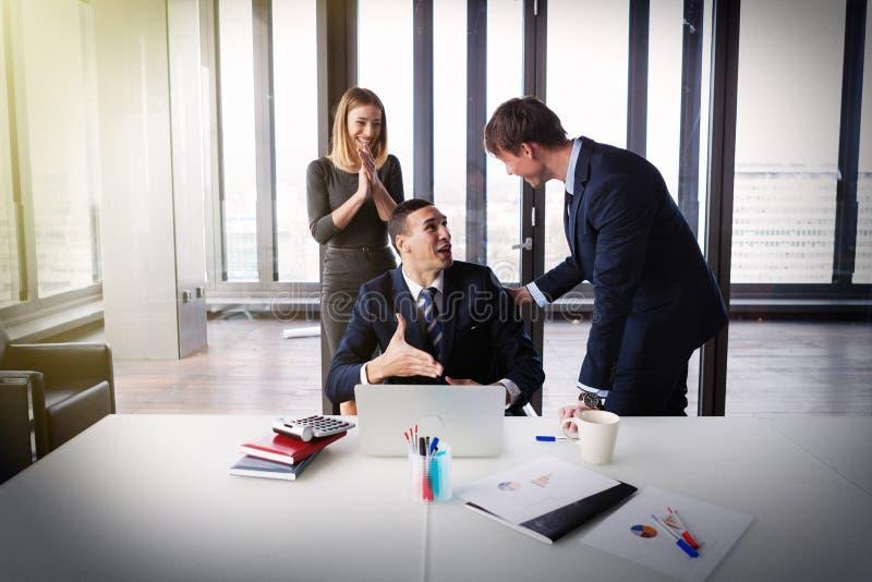 Opgewekte bedrijfsmensen in modern bureau die aan project werken royalty-vrije stock afbeeldingen