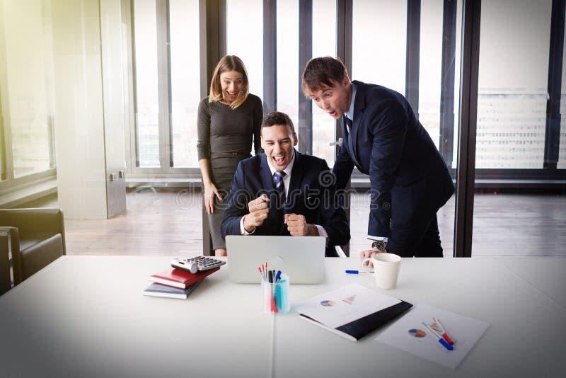 Opgewekte bedrijfsmensen in modern bureau die aan project werken royalty-vrije stock afbeelding