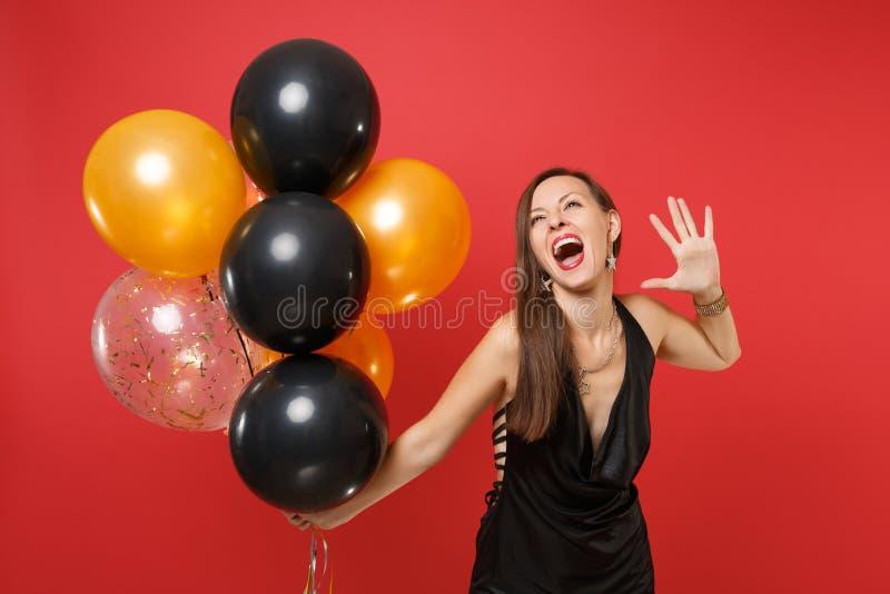 Opgewekte blije jonge vrouw in het zwarte kleding vieren, het toenemen hand, die luchtballons houdt die op rode achtergrond worde stock afbeeldingen