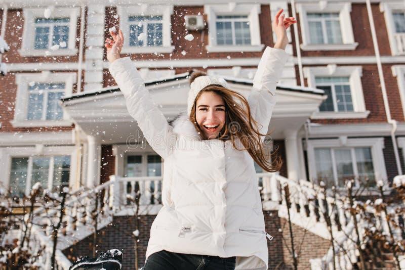 Opgewekte brightful emoties van blije vrij jonge vrouw die soround sneeuwval op straat in de wintertijd uitdrukken op huis stock afbeeldingen