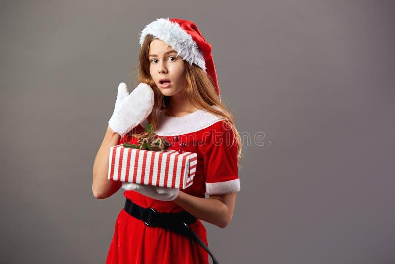 Opgewekte charmante Mevr. Claus gekleed in de de rode robe, hoed van de Kerstman en de witte handschoenen houdt de Kerstmisgift i stock foto