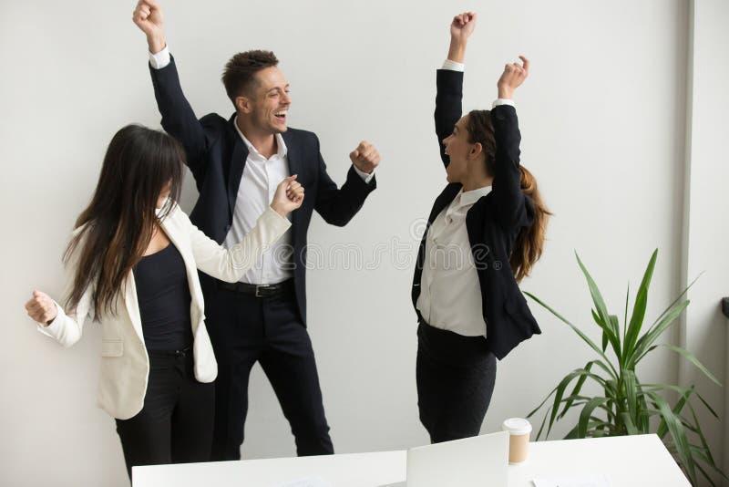 Opgewekte collega's die online winst vieren die handen opheffen stock foto's