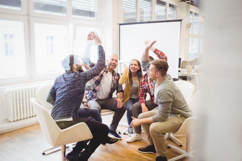 Opgewekte creatieve bedrijfsmensen die hoog-vijf geven stock foto's