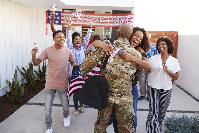 Opgewekte drie generatie Afrikaanse Amerikaanse familie die millennial militair omhelzen die huis terugkeren naar hen royalty-vrije stock foto's