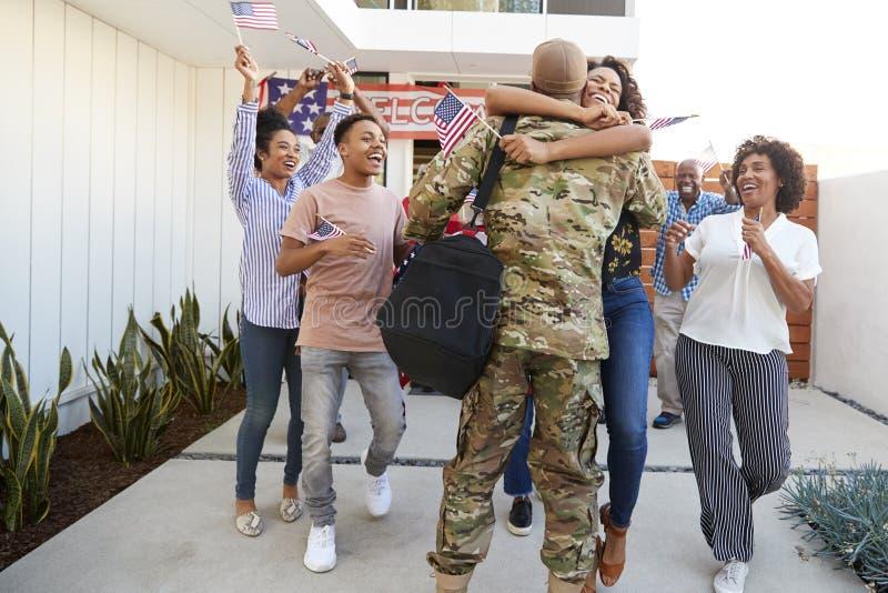 Opgewekte drie generatie Afrikaanse Amerikaanse familie die millennial militair welkom heten die huis, achtermening terugkeren stock afbeelding