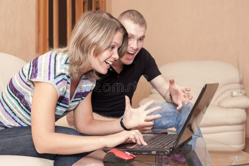 Opgewekte en gelukkige man en vrouw die het scherm van laptop, emotie tijdens speelspelen bekijken of elektronische handel of het royalty-vrije stock afbeeldingen