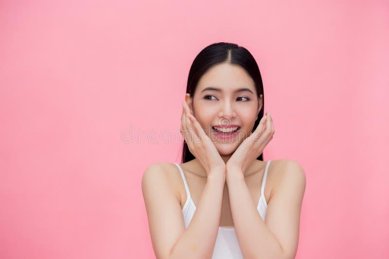 Opgewekte en verraste glimlachende Aziatische die jaren '20vrouw over roze achtergrond wordt geïsoleerd royalty-vrije stock fotografie