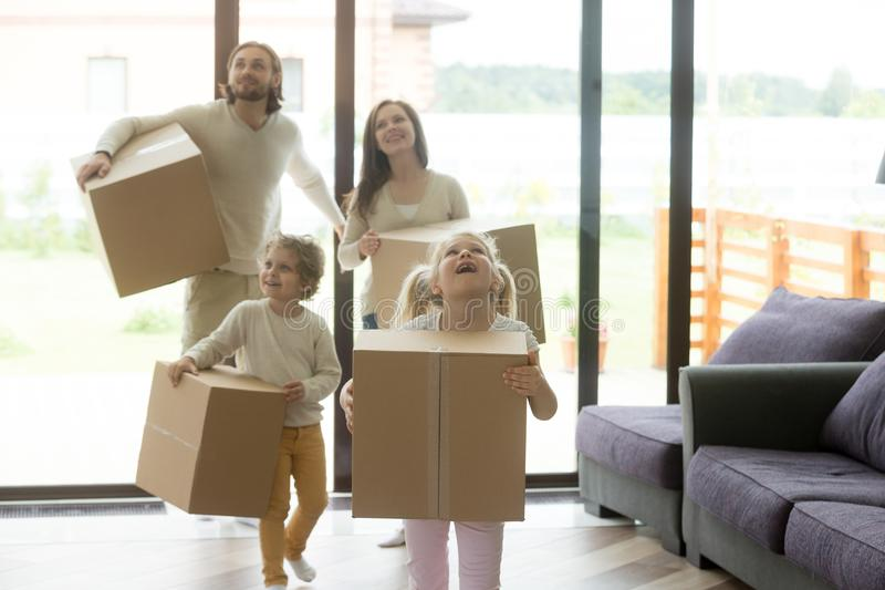 Opgewekte familiekinderen die in nieuw huis bij het bewegen van dag komen stock afbeeldingen