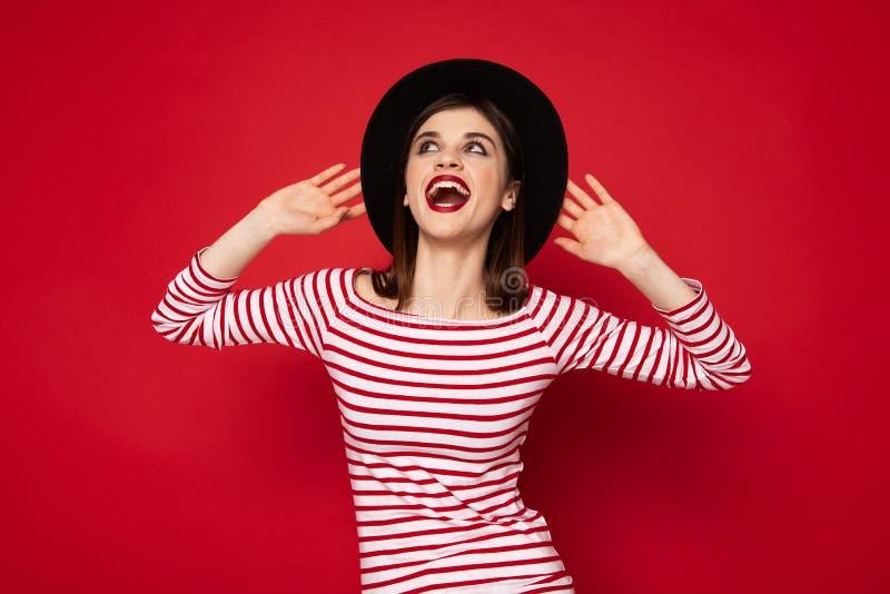 Opgewekte gelukkige dame in gestreepte blouse en schipper stock foto's