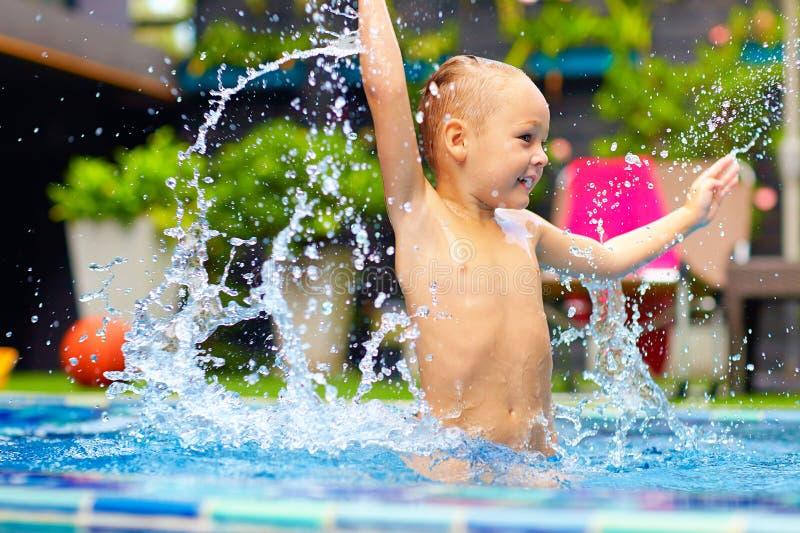 Opgewekte gelukkige jong geitjejongen die in pool, waterpret springen stock foto's