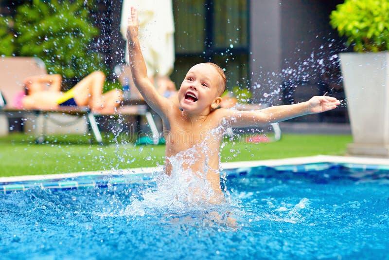Opgewekte gelukkige jong geitjejongen die in pool, waterpret springen royalty-vrije stock afbeeldingen