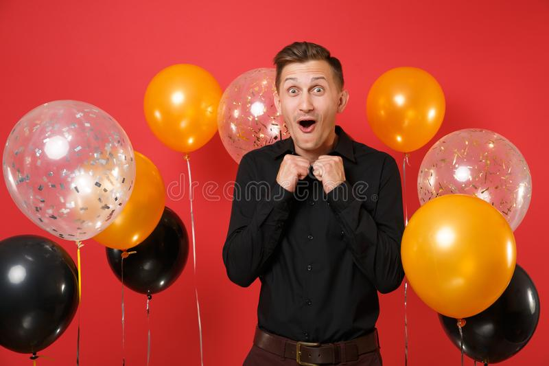 Opgewekte gelukkige jonge mens die in klassiek overhemd vuisten dichtklemmen, die op rode achtergrondluchtballons vieren St Valen stock foto's