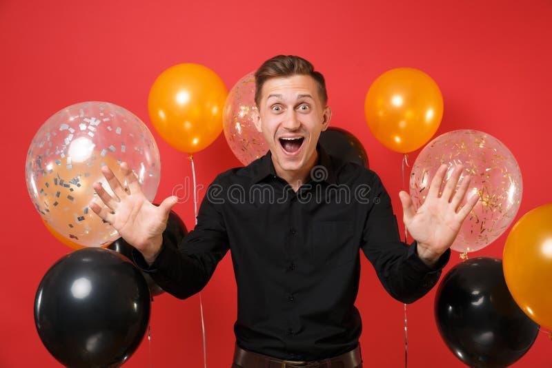 Opgewekte gelukkige jonge mens in het zwarte klassieke overhemd vieren, het uitspreiden handen, die op rode achtergrondluchtballo royalty-vrije stock foto's