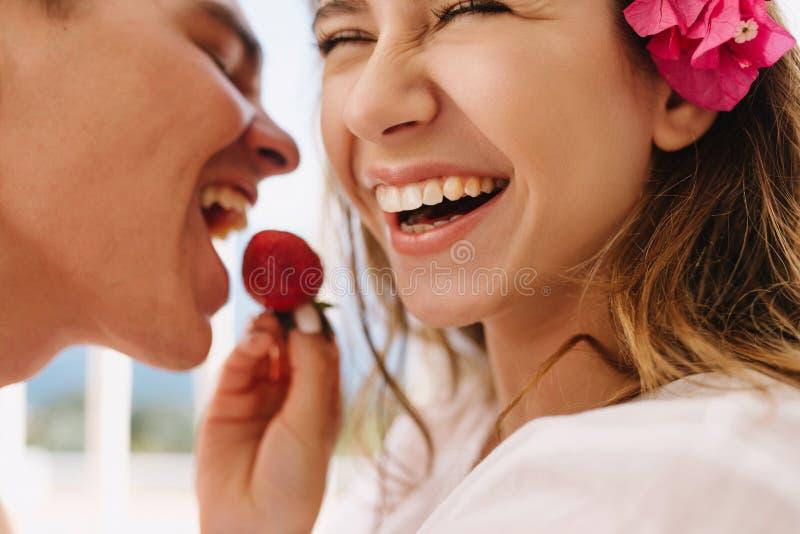 Opgewekte gelukkige jonge vrouw die met leuke roze bloem in lichtbruin haar haar lachende echtgenoot met verse aardbei voeden stock foto's