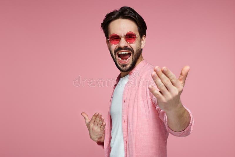 Opgewekte gelukkige mens die met geluk gillen, vierend zijn grote die triomf en overwinning, over roze achtergrond wordt geïsolee stock afbeeldingen