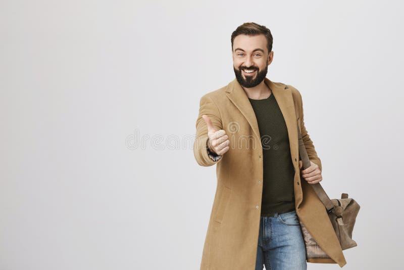 Opgewekte gelukkige volwassen mens met baard en snor die, die zak op schouder houden en laag over groene trui, het tonen dragen stock fotografie