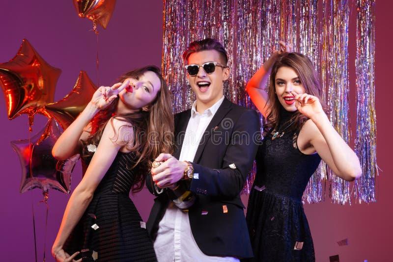Opgewekte glimlachende man en twee vrouwen die champagne openen royalty-vrije stock afbeeldingen