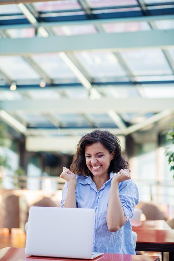 Opgewekte glimlachende vrouw die online winst vieren, die laptop in koffie met behulp van, bekijkend scherm, die met het opheffen royalty-vrije stock foto