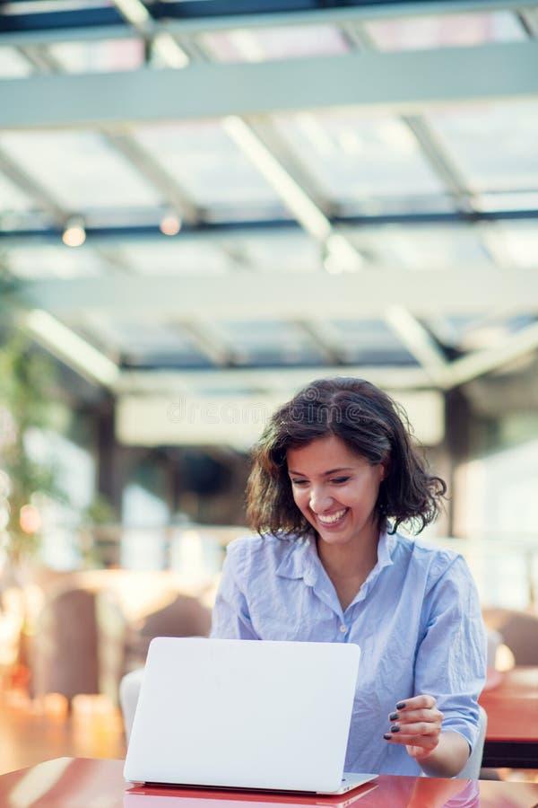 Opgewekte glimlachende vrouw die online winst vieren, die laptop in koffie met behulp van, bekijkend scherm, die met het opheffen stock fotografie