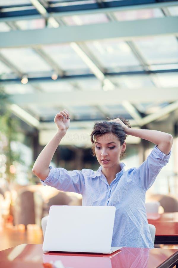 Opgewekte glimlachende vrouw die online winst vieren, die laptop in koffie met behulp van, bekijkend scherm, die met het opheffen royalty-vrije stock afbeeldingen