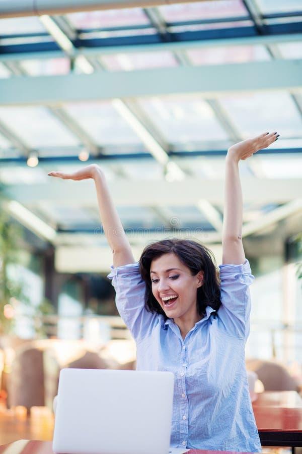 Opgewekte glimlachende vrouw die online winst vieren, die laptop in koffie met behulp van, bekijkend scherm, die met het opheffen stock afbeelding