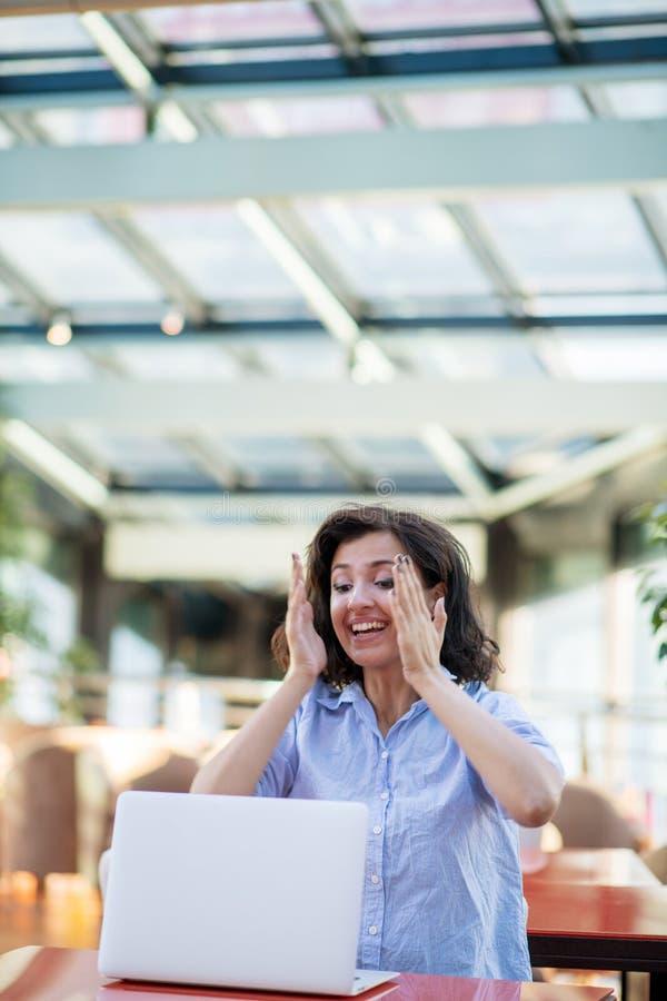 Opgewekte glimlachende vrouw die online winst vieren, die laptop in koffie met behulp van, bekijkend scherm, die met het opheffen royalty-vrije stock fotografie