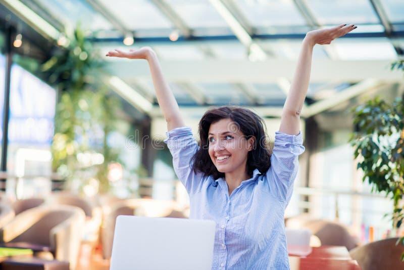 Opgewekte glimlachende vrouw die online winst vieren, die laptop in koffie met behulp van, bekijkend scherm, die met het opheffen royalty-vrije stock afbeelding