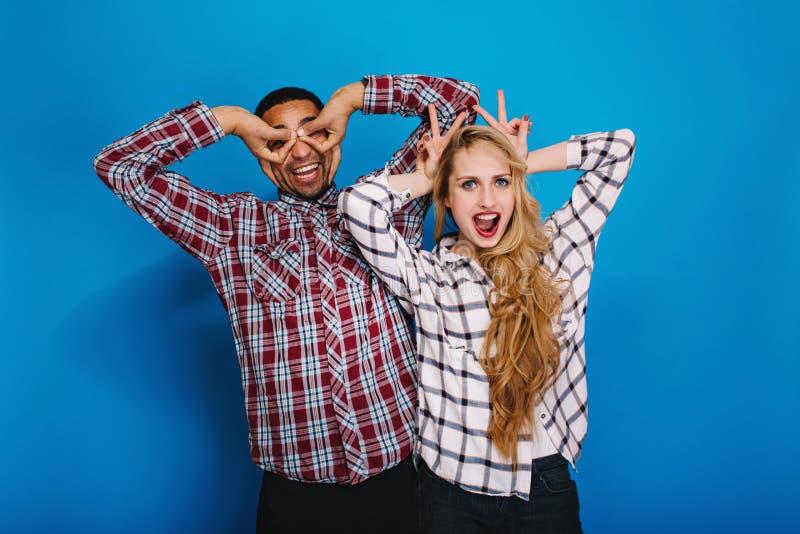 Opgewekte grappige jonge vrouw met lang blondehaar die pret met knappe kerel hebben die rond samen op blauwe achtergrond voor de  royalty-vrije stock foto
