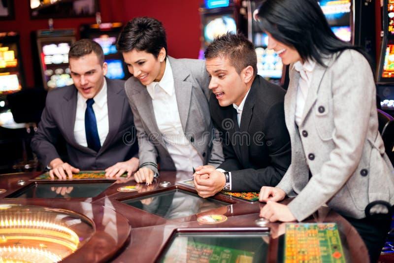 Opgewekte groep in casino stock afbeeldingen