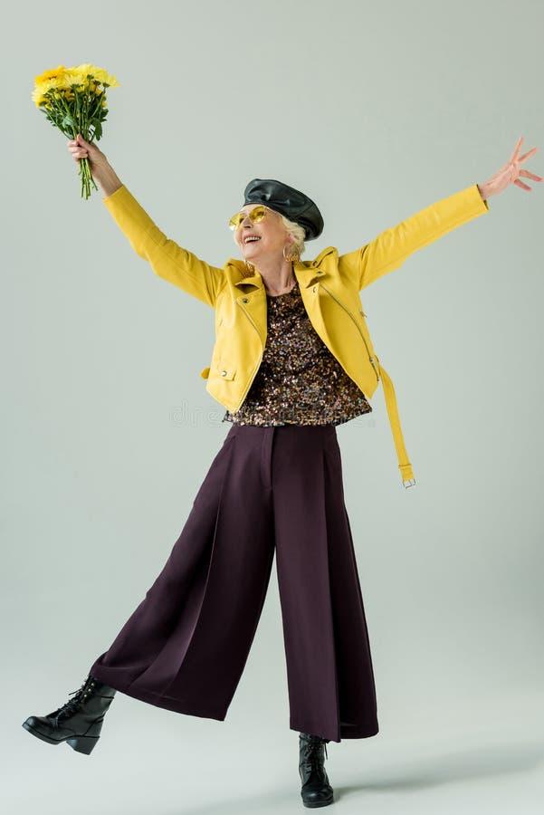 opgewekte hogere vrouw in geel leerjasje met boeket van gele bloemen, stock foto's