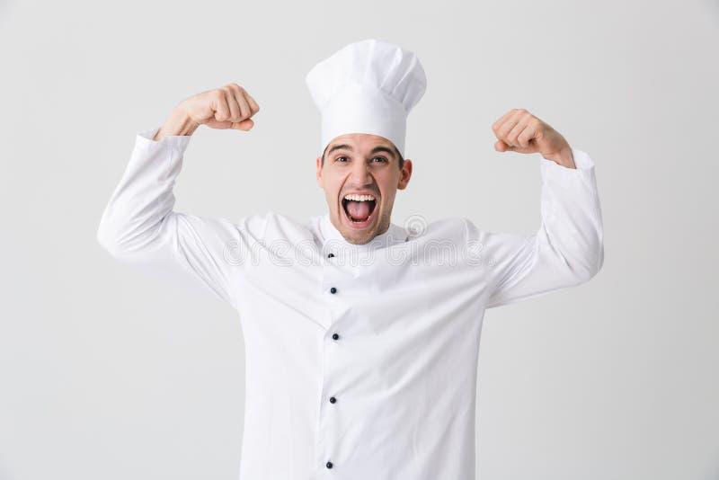 Opgewekte jonge die mensenchef-kok over witte muurachtergrond binnen wordt geïsoleerd die bicepsen tonen stock foto