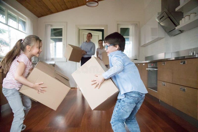 Opgewekte jonge geitjes die pret hebben die in dozen aan nieuw huis brengen stock fotografie