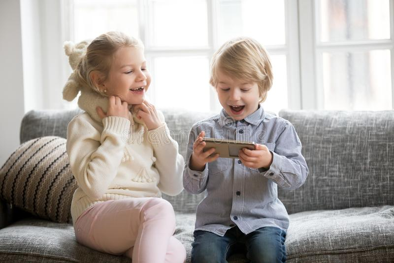 Opgewekte jonge geitjes die pret hebben die smartphonezitting samen op sof gebruiken stock afbeelding