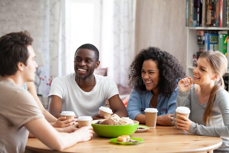 Opgewekte jonge gemengde rasmensen die aan beste vriendengrap luisteren stock foto