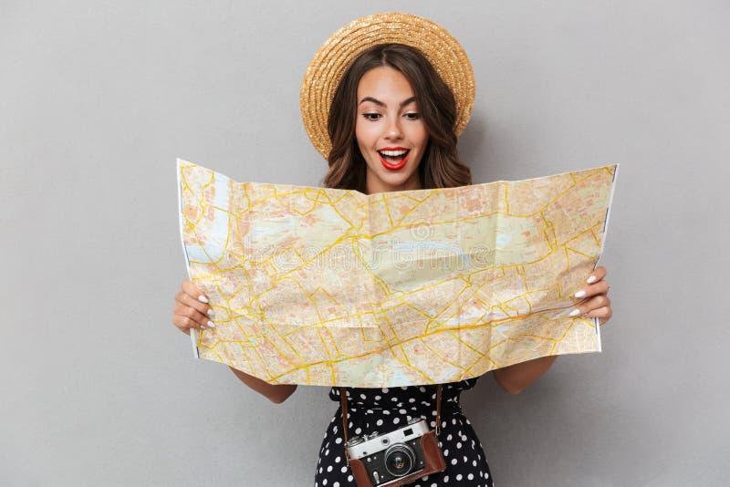 Opgewekte jonge leuke vrouw die de kaart van de hoedenholding over grijze muur dragen royalty-vrije stock afbeelding