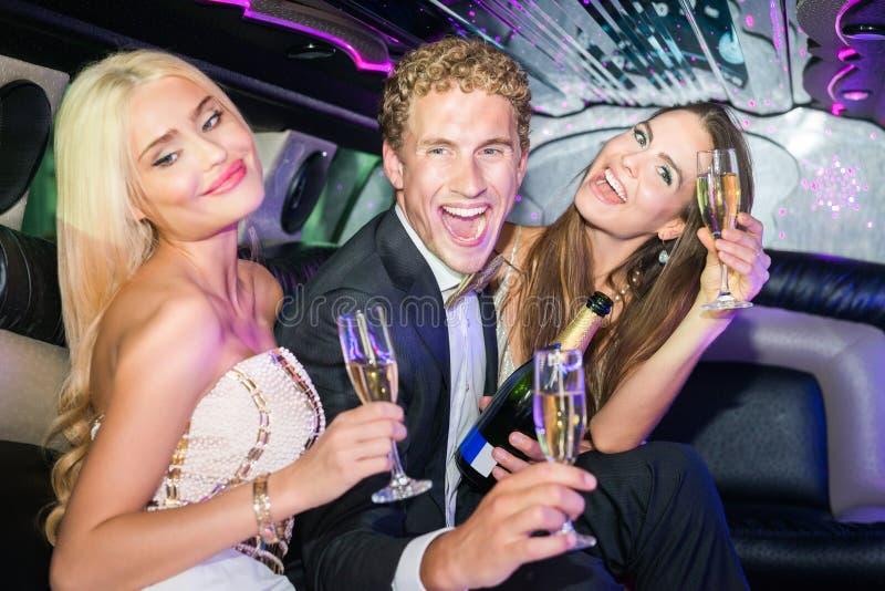 Opgewekte jonge man met vrouwen die champagnefluiten in limousi houden royalty-vrije stock afbeeldingen