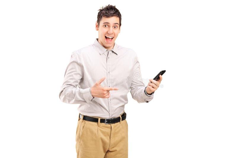 Opgewekte jonge mens die naar een celtelefoon richten royalty-vrije stock afbeeldingen