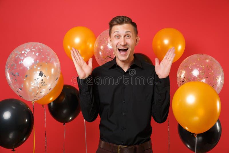 Opgewekte jonge mens in zwarte klassieke overhemd het uitspreiden handen, die op rode achtergrondluchtballons vieren St Valentine royalty-vrije stock foto's