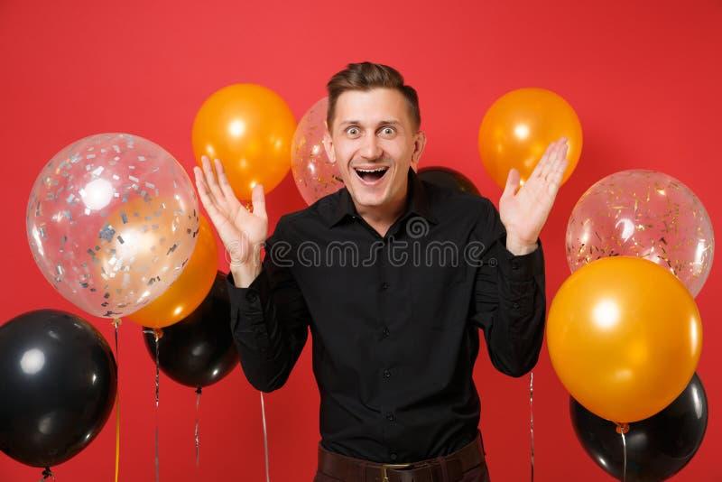 Opgewekte jonge mens in zwarte klassieke overhemd het vieren het uitspreiden handen op heldere rode achtergrondluchtballons Valen royalty-vrije stock afbeeldingen