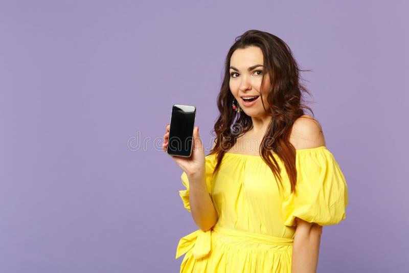 Opgewekte jonge vrouw die in gele de zomerkleding mobiele telefoon met het lege lege die scherm houden op pastelkleurviooltje wor royalty-vrije stock fotografie