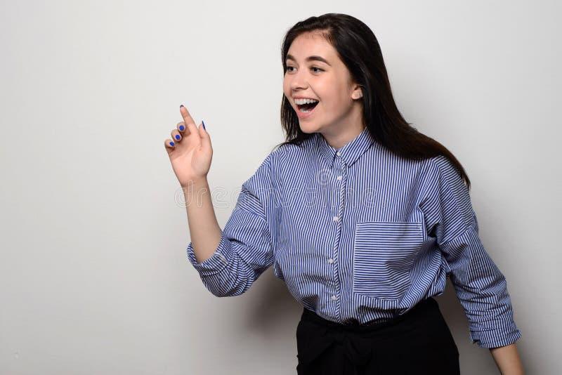 Opgewekte jonge vrouw die haar vinger naar lege ruimte richten die zich bij witte muur bevinden royalty-vrije stock afbeeldingen