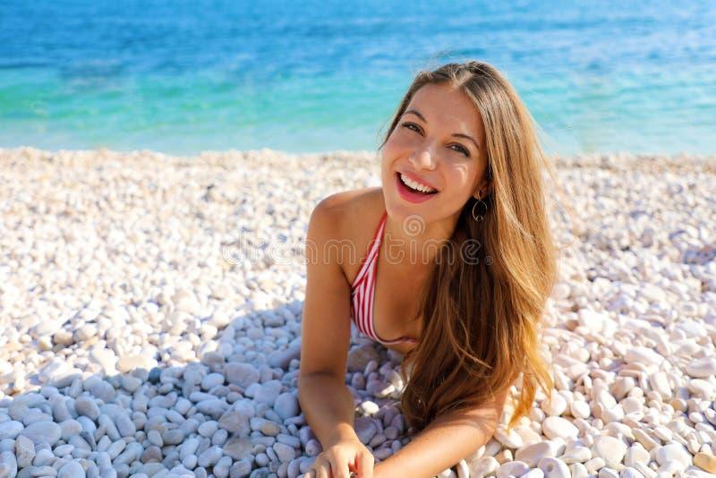 Opgewekte jonge vrouw die op kiezelstenenstrand ligt Sluit omhoog portret van gelukkig meisje op haar de zomervakantie De ruimte  stock afbeelding