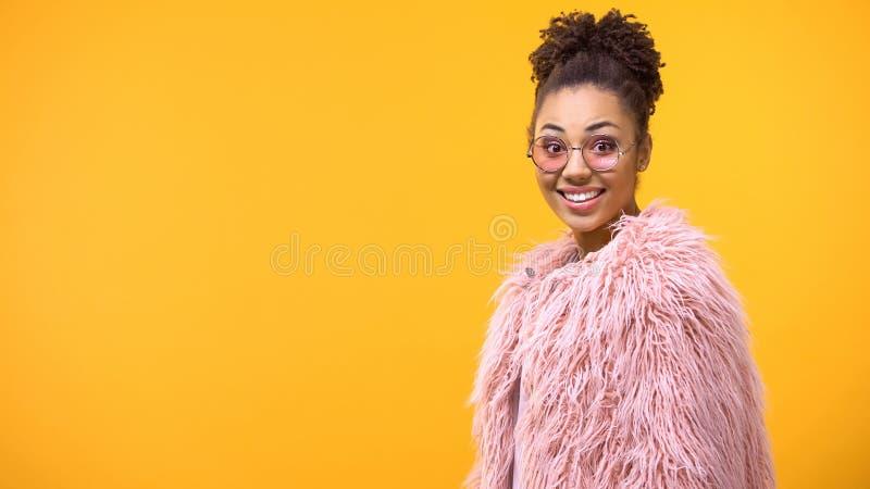 Opgewekte jonge vrouw die in roze oogglazen camera, verbazing, geluk kijken stock afbeeldingen
