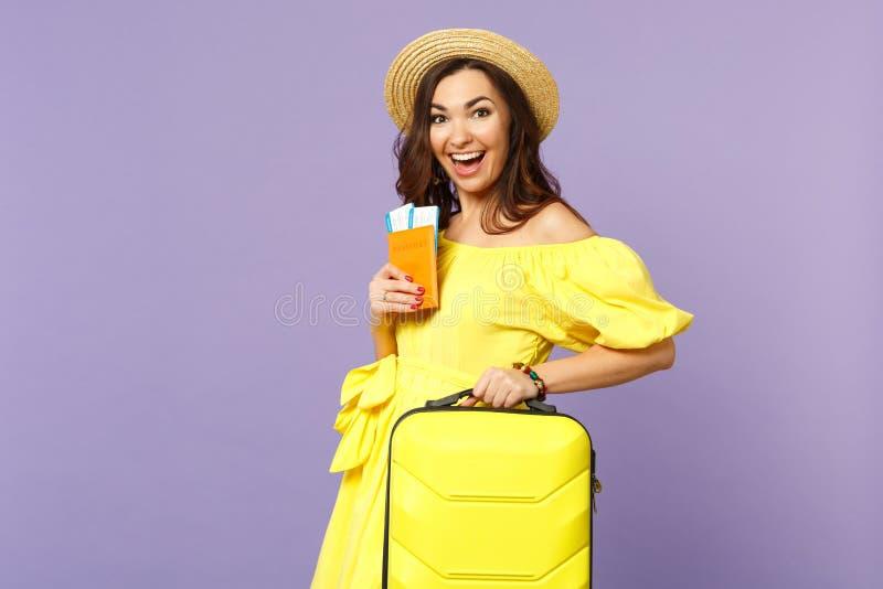 Opgewekte jonge vrouw in gele die kleding, de greepkoffer van de de zomerhoed, het kaartje van de paspoort instapkaart op pastelk stock fotografie