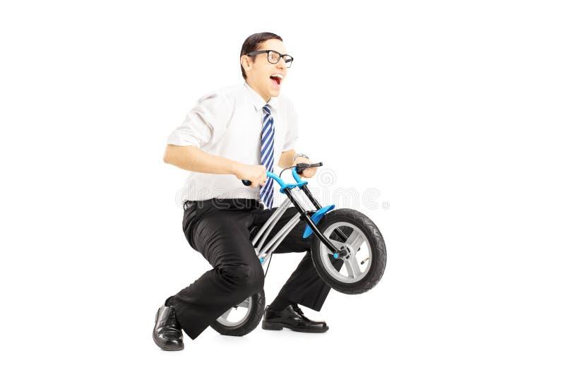 Opgewekte jonge zakenman die een kleine fiets berijdt stock fotografie
