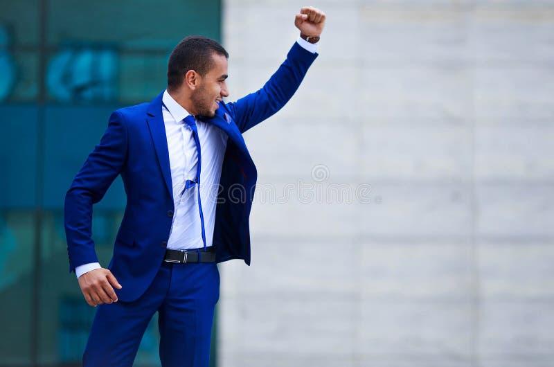 Opgewekte jonge zakenman die zich in openlucht bij de bureaubouw B bevinden royalty-vrije stock foto