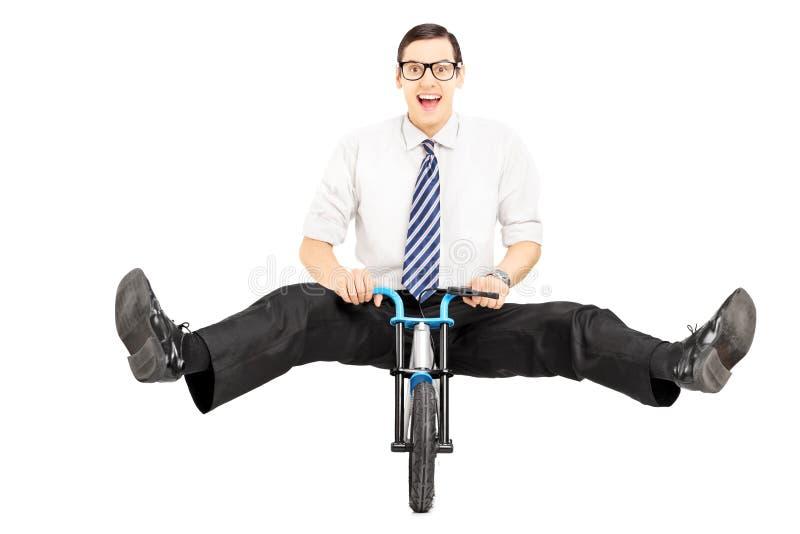 Opgewekte jonge zakenman met band die een kleine fiets berijden royalty-vrije stock foto's